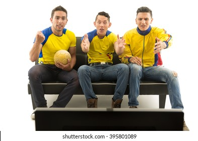 Three friends sitting on sofa wearing yellow sports shirts watching television with enthusiasm, white background, shot from behind tv