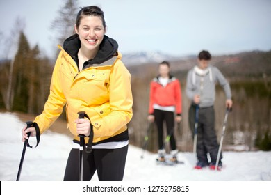 Three friends snowshoeing in park with low depth of field