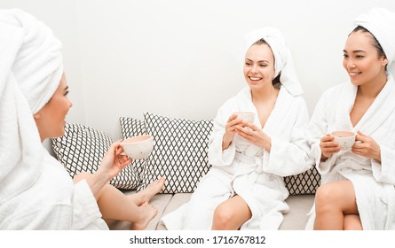 Three friends at the spa. Beautiful women wearing bathrobes speaking and drink tea in the spa, after relaxes procedures. Pampering your body