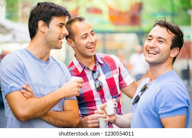 Three friends talking and having fun while drinking coffee outdoor