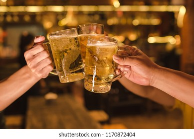 Three friends toasting with glasses of light beer at the pub. Beautiful background of the Oktoberfest. fine grain. Soft focus. Shallow DOF