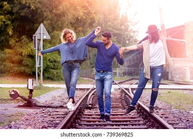 three friends walking on train tracks and having fun