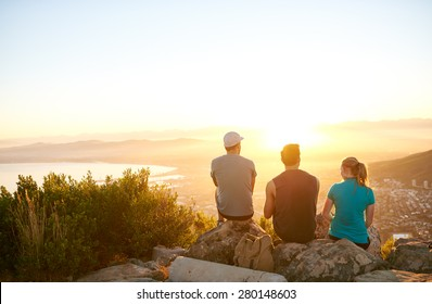 Three friends watching the sunrise over the city together from a mountain nature trail