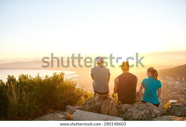 Drei Freunde, die den Sonnenaufgang über der Stadt beobachten, zusammen mit einem Naturlehrpfad