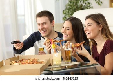 Three friends watching tv and eating pizza sitting on the floor in the living room in a house interior