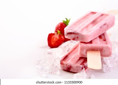 Three frozen popsicles with fresh strawberry ingredients stacked chilling on a bed of crushed ice with copy space alongside
