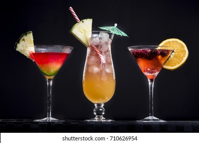 Three fruit cocktails, red and orange, stand against a black background.
