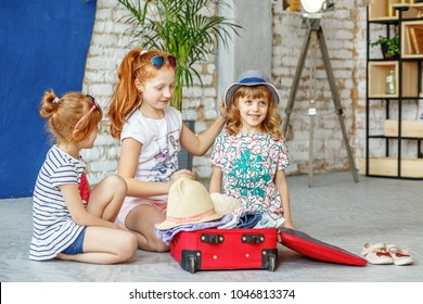 Three fun children pack a suitcase for a beach holiday. Concept, lifestyle, childhood, trip, vacation, family tourism