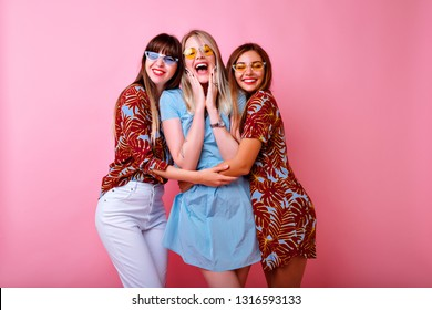 Three funny blithesome girls having fun together, hugs and smiling, best friends relationship, happy exited emotions, stylish feminine summer clothes, pink background.