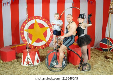 Three funny circus strong man, woman in cylinder and boy on retro bike with balloons in striped tent