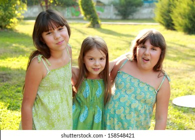Three funny happy little girls fool around in the park