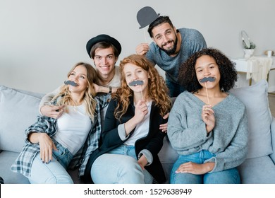 Three funny intercultural girls with moustaches on sticks sitting on couch with two happy guys standing behind