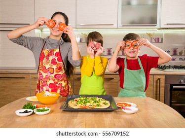 Three funny kids with food on eyes making the pizza, in the kitchen interior