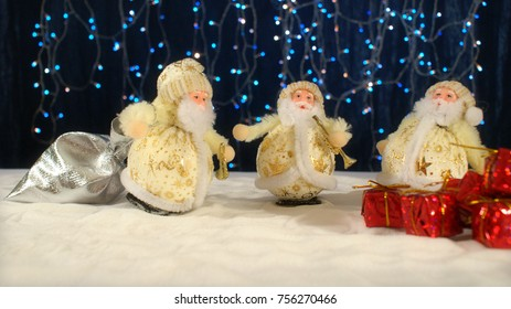 Three funny Santa Clauses-musicians are congratulating on the New Year on the snow with their gifts