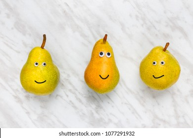Three funny smiling pears on marble background. Different personalities.