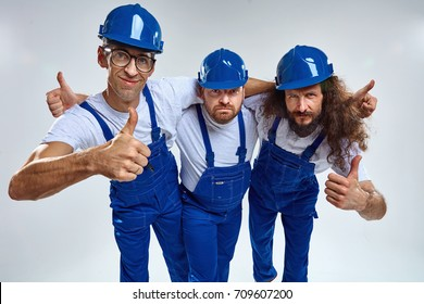 Three funny young builders - isolated portrait