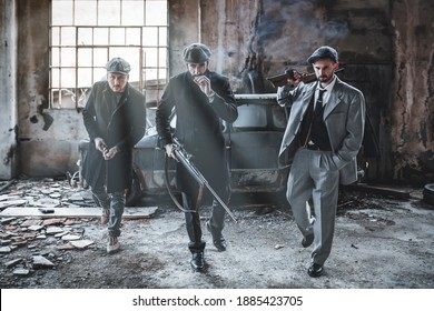 Three gangsters with firearms and dangerous in hand. Men in vintage clothing and guns. Abandoned factory background.