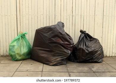 Three garbage bags at old wood panel