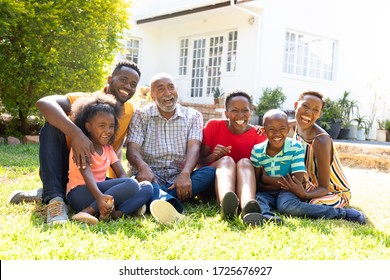 Three generation African American family spending time in their garden on a sunny day, sitting on a lawn and smiling.