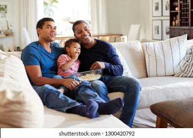 Three generation African American  male family group sitting on a sofa in the living room eating popcorn and watching TV, selective focus
