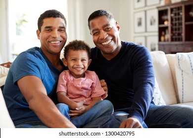 Three generation African American male family group sitting on a sofa in the living room looking to camera, close up