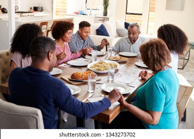 Three generation black family sitting at dinner table holding hands and saying grace before meal