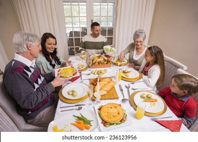 Three generation family having christmas dinner together at home in the living room