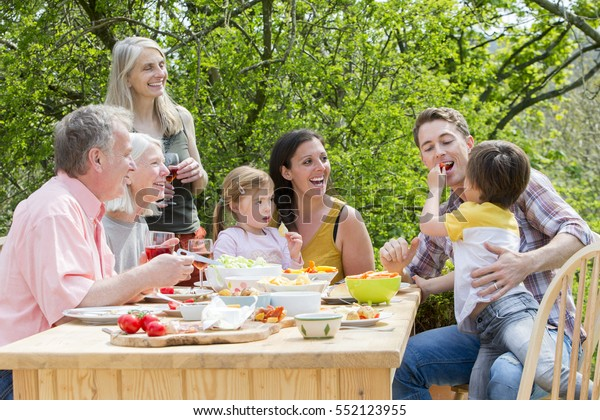 Three generation family having a garden party in the summer. Everyone is laughing and looking at the little boy, who is feeding his father some red pepper.