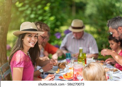 Three generation family lunching in the garden in summer, the table is set up with dishes very colorful. Focus on a beautiful young woman looking at camera. Shot with flare