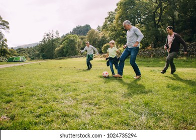 Three generation family are playing football together in a field. There are two boys, their father and their grandfather.