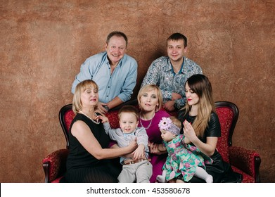 Three Generation Family Sitting On Sofa Together. Classic portrait