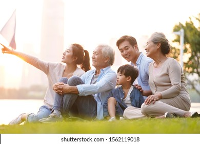 three generation happy asian family sitting on grass enjoying good time at dusk outdoors in park