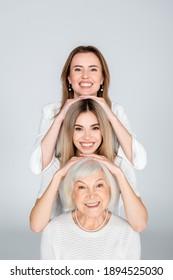 three generation of happy women isolated on grey