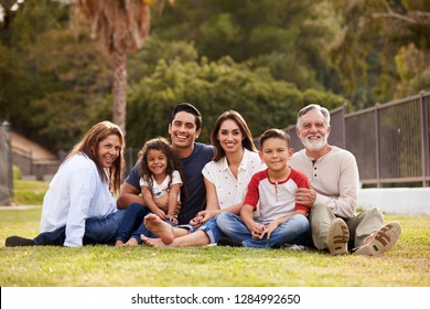 Three generation Hispanic family sitting on the grass in the park smiling to camera, selective focus