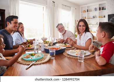 Three generation Hispanic family sitting at the table eating dinner