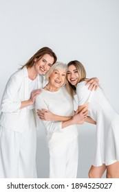 three generation of pleased women smiling while looking at camera and hugging isolated on grey