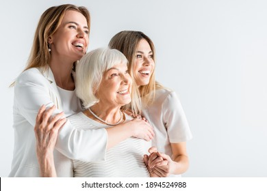 three generation of positive women smiling while hugging isolated on white