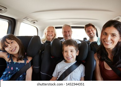 Three generation white family sitting in two rows of passenger seats in a car, smiling to camera