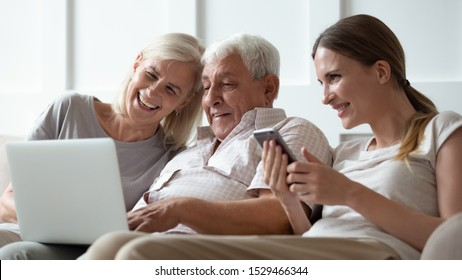 Three generations family with gadgets at home, seated on sofa adult daughter with smartphone and elderly parents using computer, different age people users and modern wireless technology usage concept