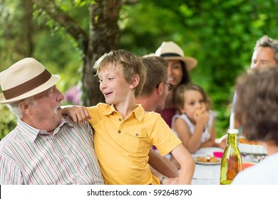 Three generations family gathered to lunch in the garden. focus on grandfather with her grandson on his knees