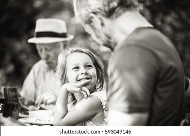 Three generations family gathered to lunch in the garden in summer, focus on a beautiful little girl looking at her dad. Black and white