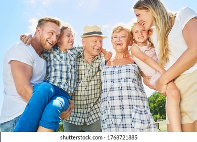 Three generations of family with grandparents and children laughs happily at the camera