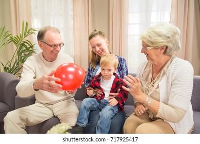 Three generations family having fun while sitting on sofa indoors