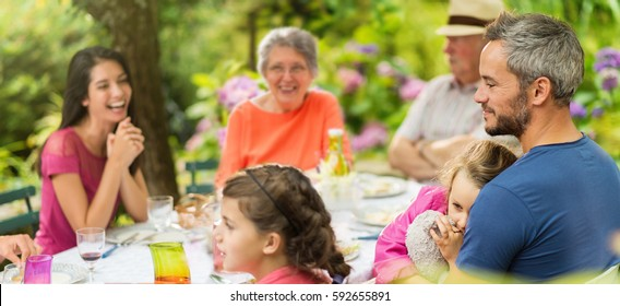 Three generations family having lunch in the garden family having lunch in the garden, A little girl falling asleep in her father's arms