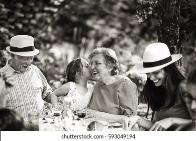 Three generations family having lunch in the garden, a little girl whispers a secret in her grandmother's ear. Black and white