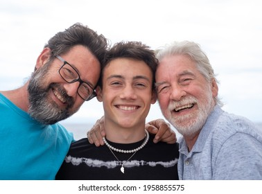 Three generations of family, hug smiling happy, father, teenage son and grandfather. Handsome people having fun together