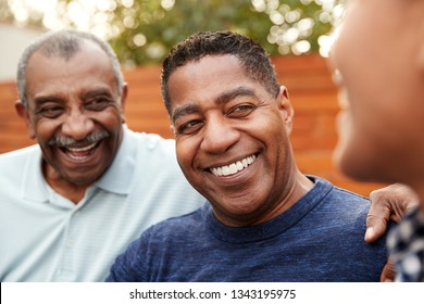 Three generations of family men laughing together, close up