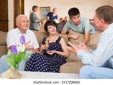 Three generations of happy family carefree communicating in comfortable apartment..