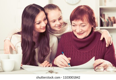 Three generations of happy family working together with documents at home