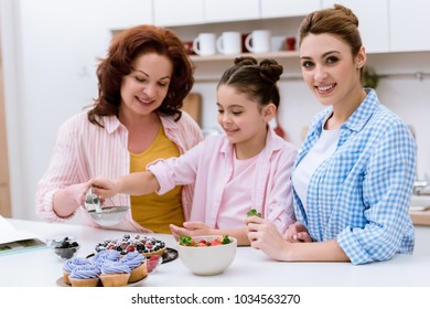 three generations of happy women pouring sugar onto tart with berries together at kitchen